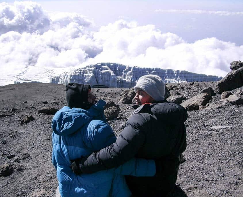 Luke sitting on the summit after climbing Mount Kilimanjaro