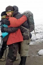 Cameron Kirkpatrick thanking our local guide with a big hug after he summited Kilimanjaro on the Peak Potential Adventures Kilimanjaro trek.