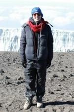 Kristen Forbes getting a photo on the summit of Kilimanjaro on the Peak Potential Adventures Kilimanjaro trek.